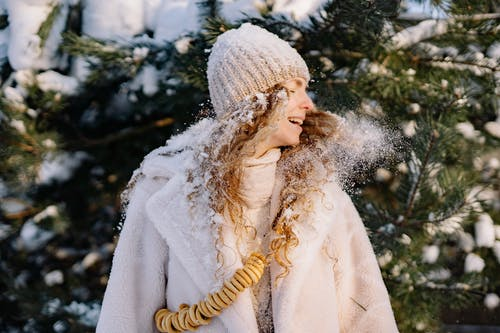 Close-Up Photo of a Woman Flipping Her Hair with Snow