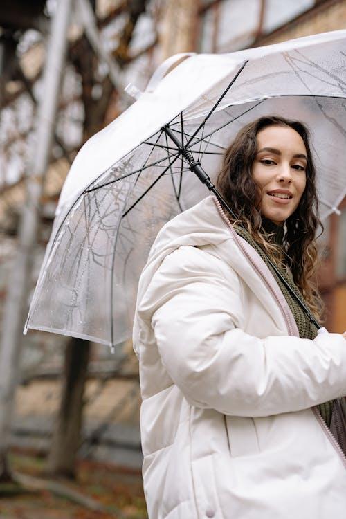 Woman in White Coat Holding Umbrella