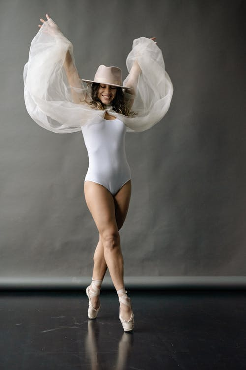A Woman in a White Leotard And a Cowboy Hat Dancing