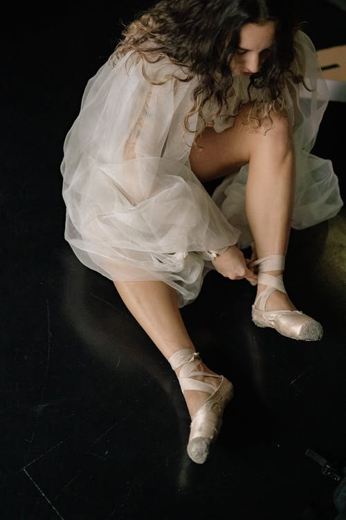 A Woman Fixing Her Ballet Shoes While Sitting on the Floor