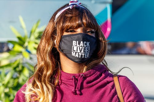 Woman in Pink Crew Neck Shirt Wearing Black and White Mask