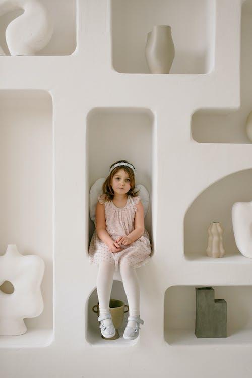 Girl in Angel Costume Sitting on the Shelf