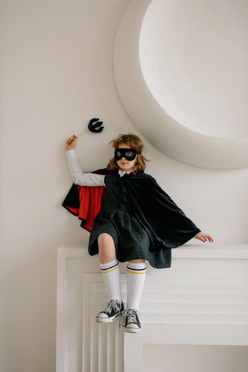 Girl in Devil Costume Sitting on Top of Fireplace