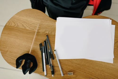 White Paper and Pens on Wooden Table