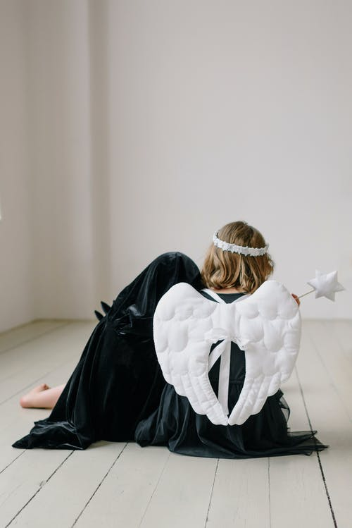 Girl with Angel Wings Sitting on the Floor