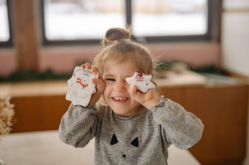 Girl in Gray Sweater Holding Cookies and Smiling