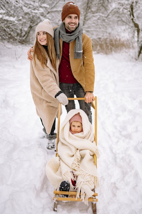A Happy Family Standing on Snow-Covered Ground