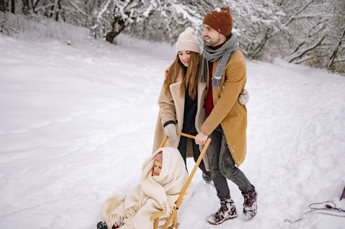 A Happy Family Walking on Snow-Covered Ground