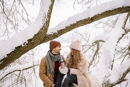 A Lovely Couple in Winter Clothes Looking at Each Other under the Snow-Covered Tree Branch