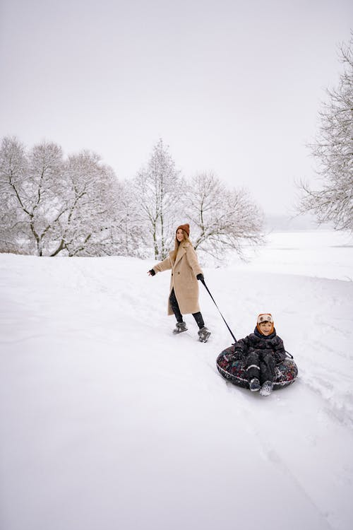 A Family Having Fun Playing in the Snow-Covered Ground