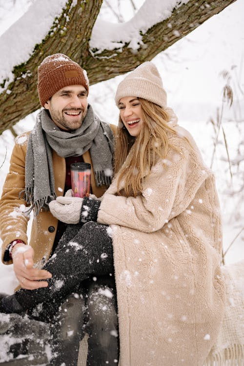 A Lovely Couple in Winter Clothes Having Fun during Winter