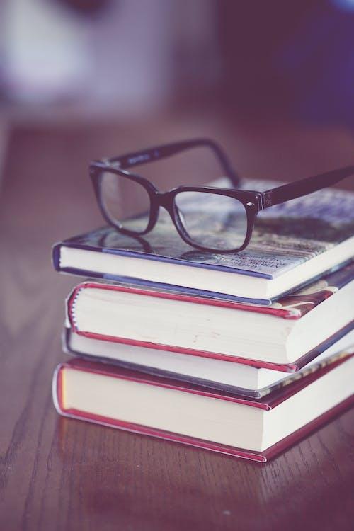 A Black Framed Eyeglasses on Stack of Books