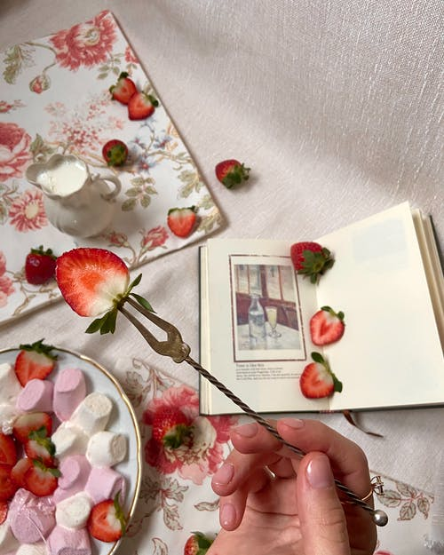 Crop woman with strawberry near book