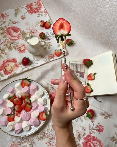 Person Holding White Paper With Red Rose Petals