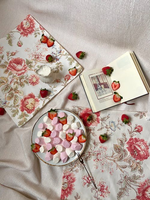 Top view of plate full of colorful marshmallows and slices of fresh strawberry placed on textile with jug of milk and book in stylish room