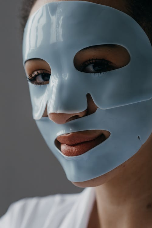 Close-Up Photo of a Woman with Facial Mask while Looking at Camera