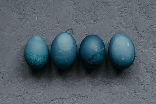 Close-Up Photo of Blue Easter Eggs on Gray Surface