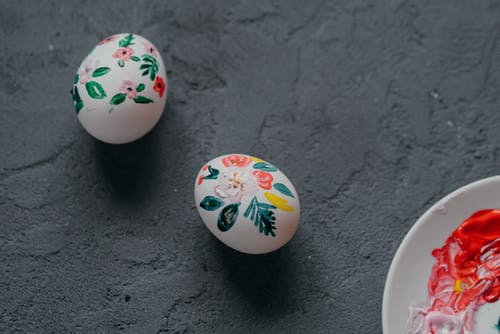 Top view of white chicken eggs decorated with painted colorful floral ornament laced in rough gray table during Easter preparation