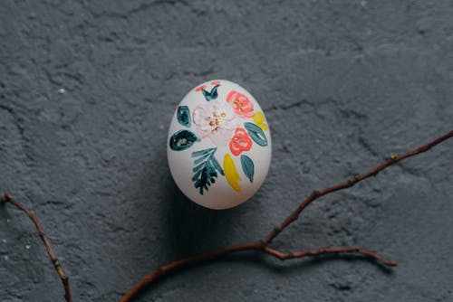 Handcrafted Easter egg with tree twig placed on table