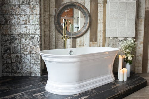 White bath with golden faucet placed near burning candles and green plants in vase near wall with mirror in modern bathroom