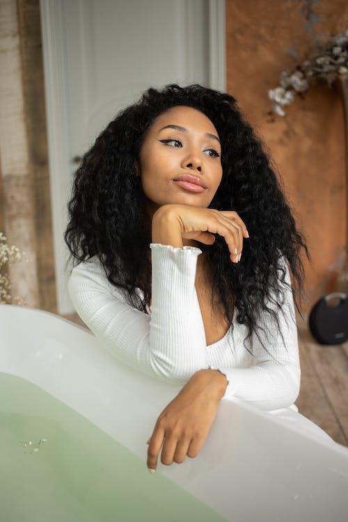 Black woman sitting near bathtub