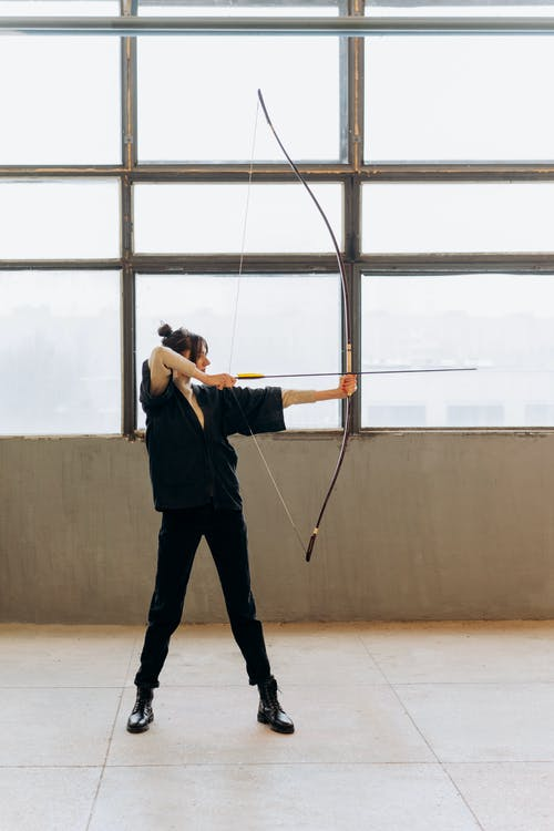 Man in Black T-shirt and Black Pants Holding Bow