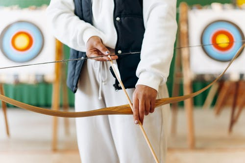 Man in White Dress Shirt Holding Brown Wooden Stick