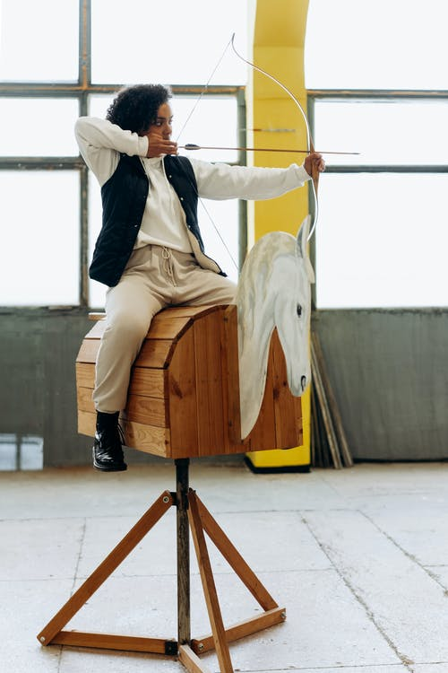 Man in Gray Blazer and Brown Pants Sitting on Brown Wooden Seat