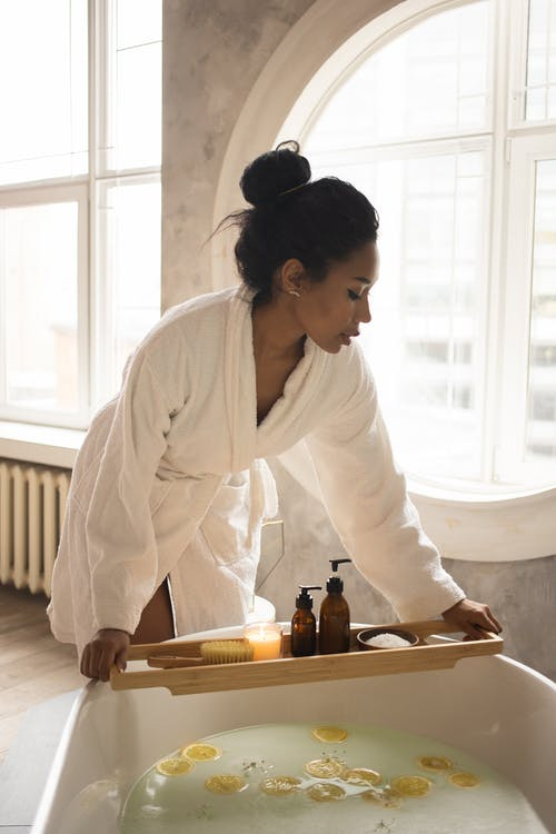 African American female in white bathrobe putting wooden tray with spa products on bathtub with lemon slices during skin care routine