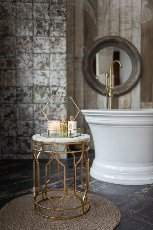 Glass box with spa supplies placed on small round table near white bathtub in stylish bathroom near wall with mirror
