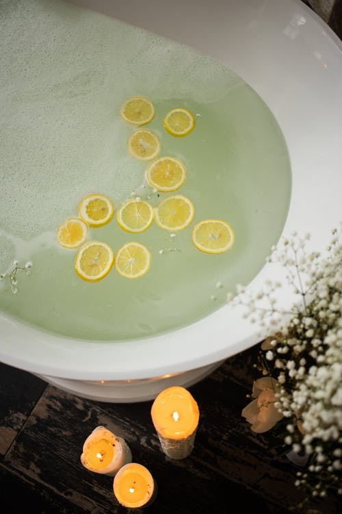 From above of white tub with clear water near burning candles and blooming flowers in modern bathroom during skincare treatment