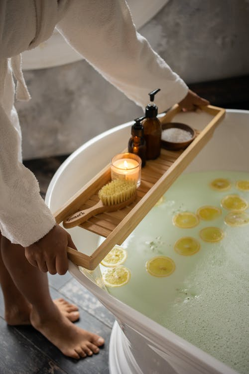 Unrecognizable barefoot female in bathrobe putting wooden tray with spa supplies on tub with lemon slices on water surface during skincare routine