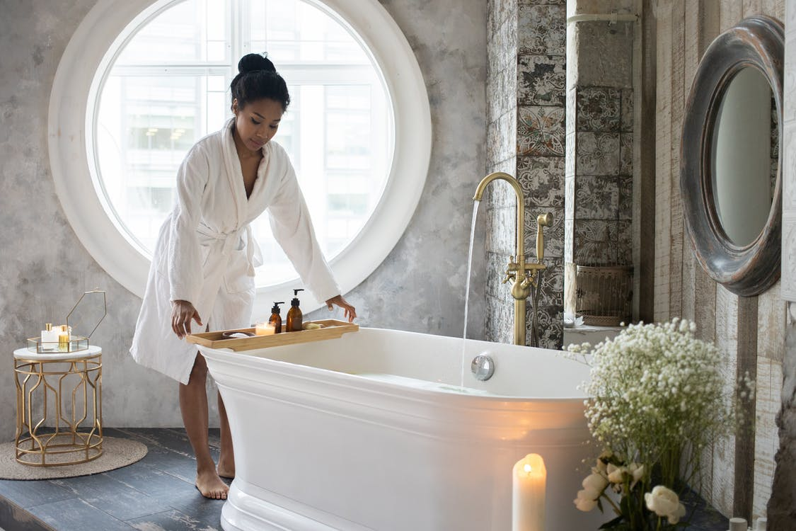 Full body of barefoot African America female in bathrobe putting wooden tray with spa supplies on bath during spa procedure