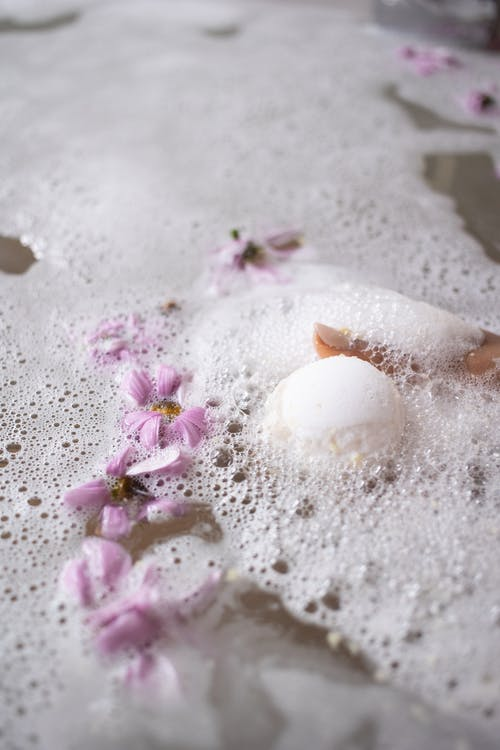 White ball of bath salt on water surface with foam