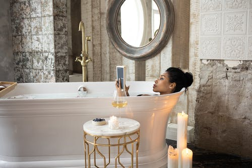 Side view of young African American female reading book while lying in bathtub and enjoying spa procedure with wine glass on small marble table and aroma candles