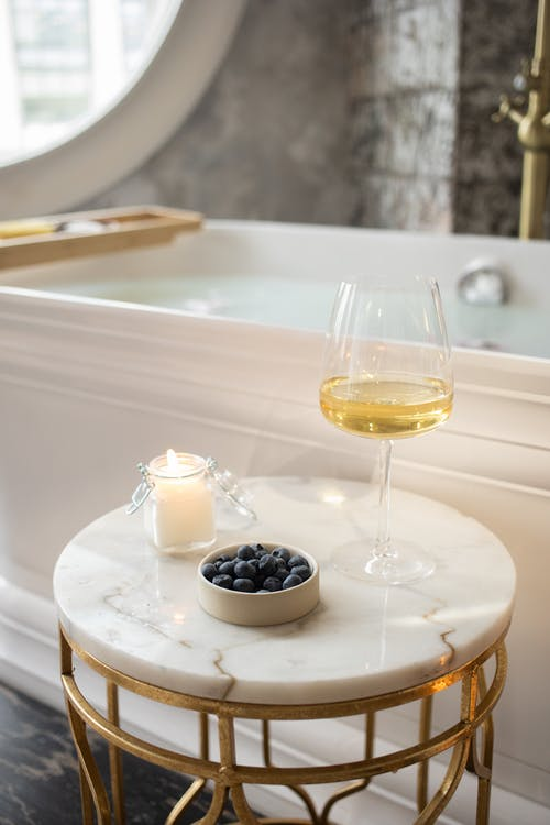 Round table with wineglass burning candle and berries in bathroom