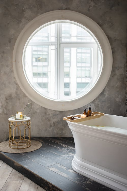 Interior of contemporary bathroom with white bathtub and small table placed against concrete wall with round window in daylight