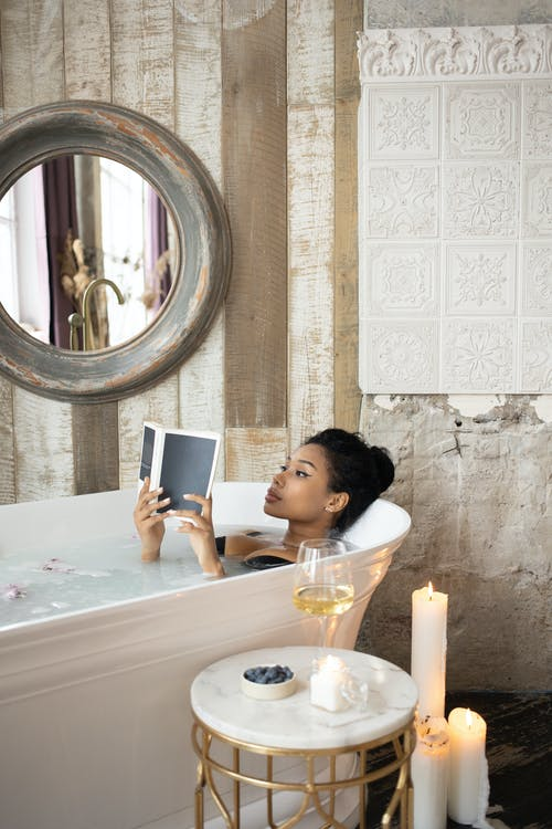 Young black woman reading book in bath