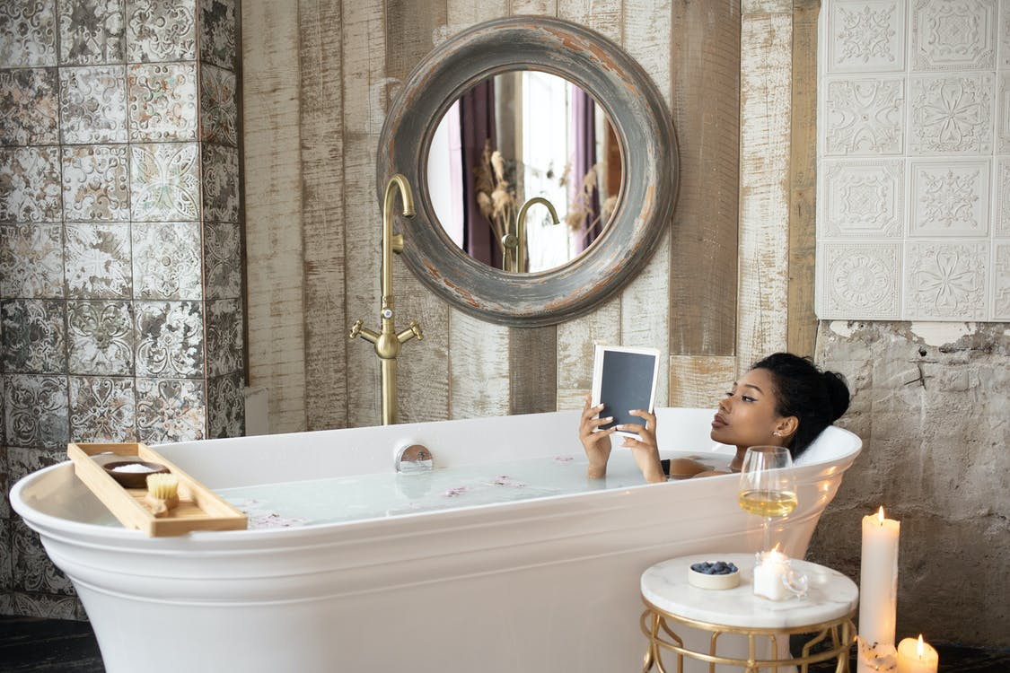 Young African American female reading book while taking bath in light bathroom with burning aromatic candles placed near round table with wineglass and berries on background of shabby stone walls
