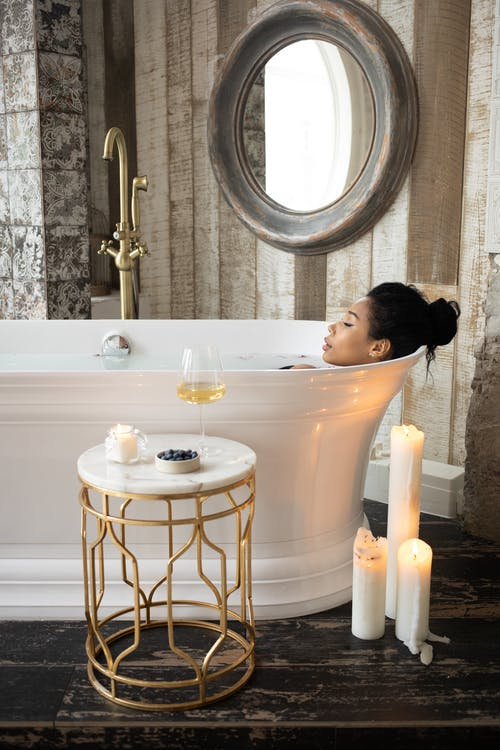 Side view of young ethnic female lying in bathtub with closed eyes in light bathroom with candles and table on background of mirror