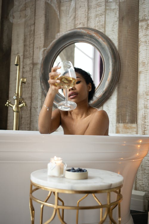 Young sensual ethnic female toasting with glass of white wine sitting in bathtub in light bathroom with candles and table on background of round mirror