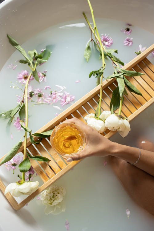 Top view of anonymous female with white wine sitting in bathtub with pink and white flowers