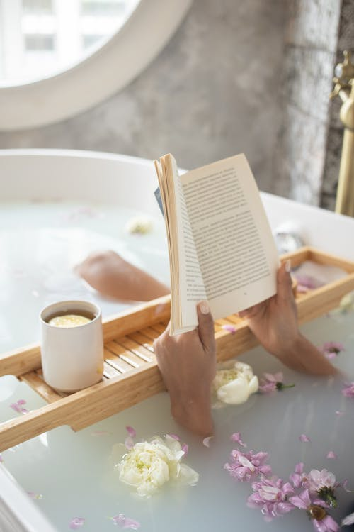 From above of unrecognizable female lying in bathtub full of water with delicate ivory and pink flowers and reading book on blurred background