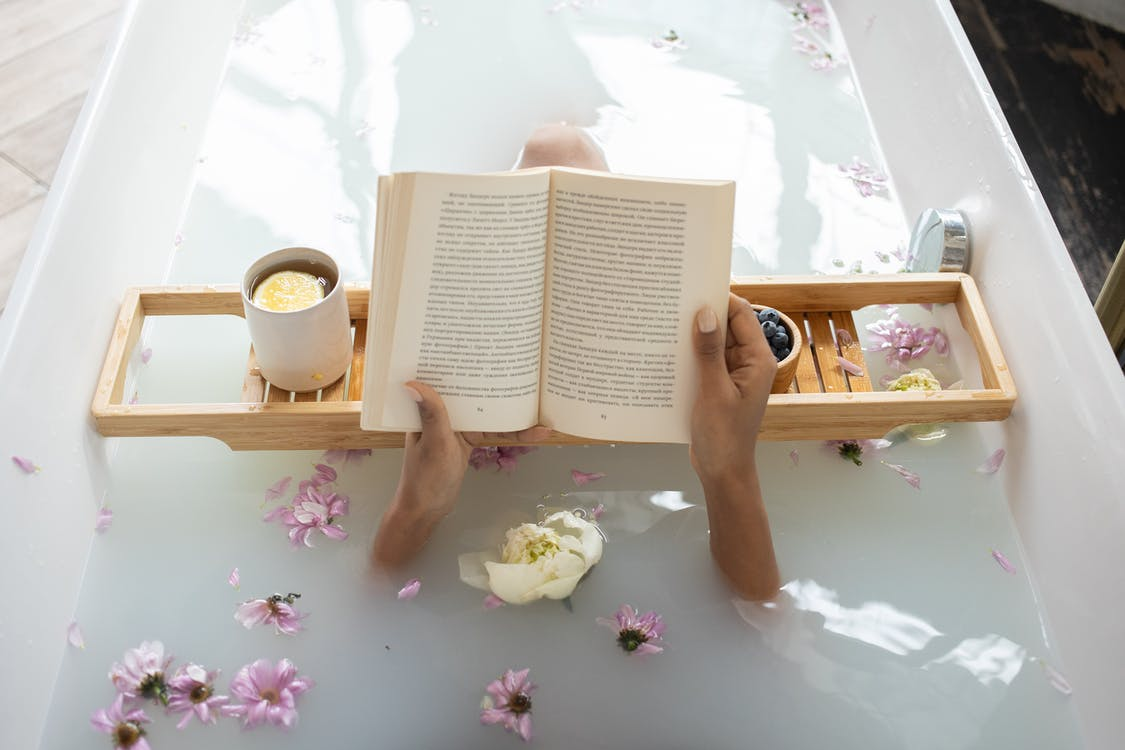 Woman reading book while resting in bathtub
