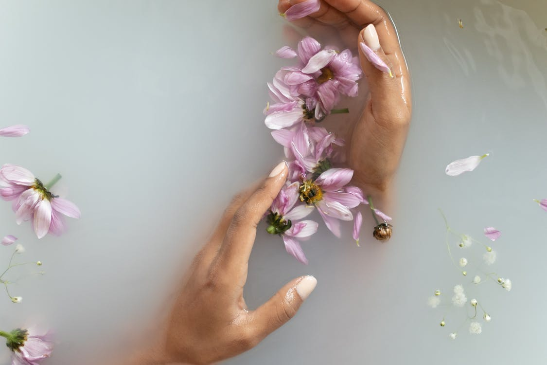 Woman holding flowers in hands in water