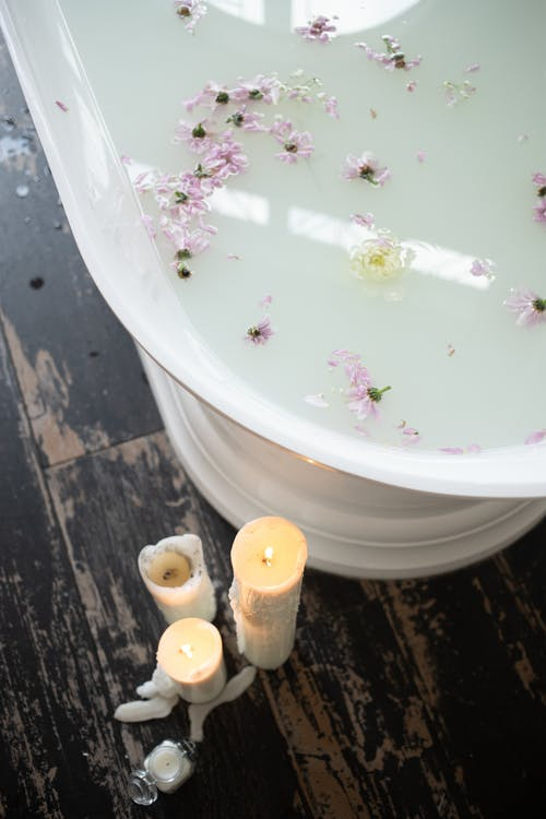 Bathroom with candles and white water with flower petals