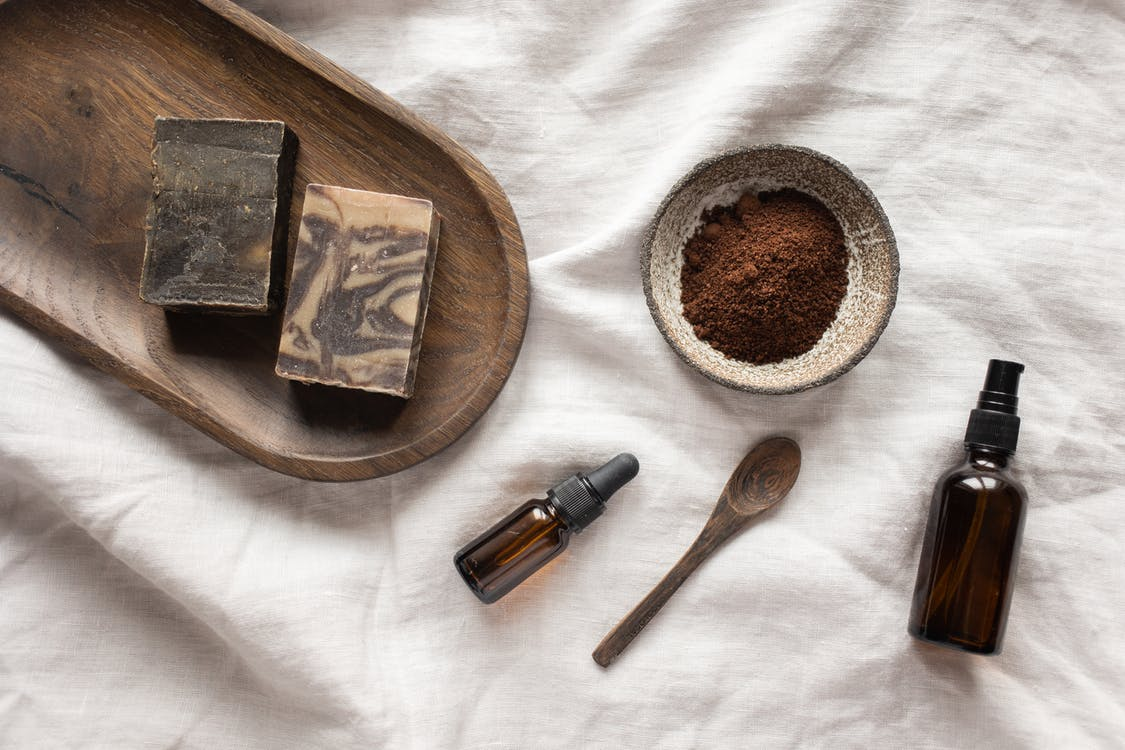 Top view of coffee scrub in bowl composed with bottles of aromatic oil on white sheet