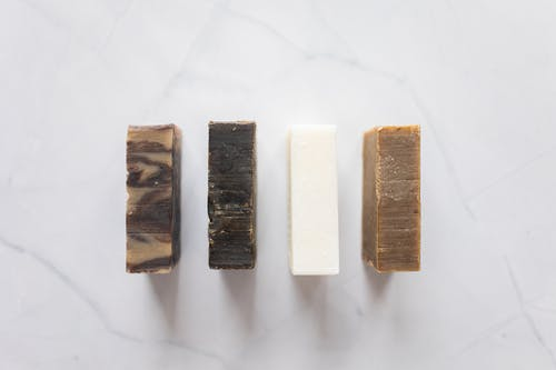 Top view of composition with handmade aromatic soap placed on white background in bathroom