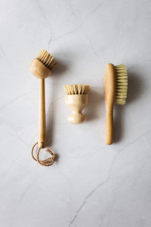 Top view of timber dry brushes for bathing and cleaning on white background