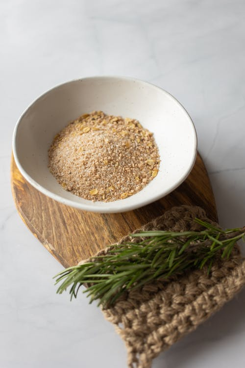 From above of white bowl filled with powder of oat flakes near fresh verdant branch of rosemary on timber board